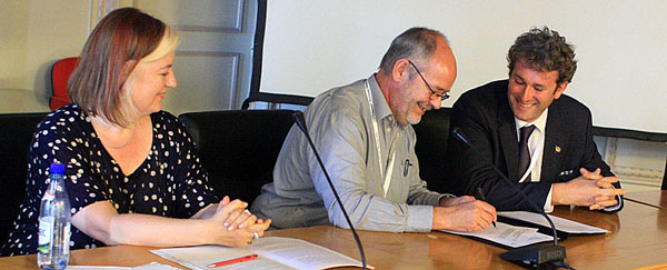 Bert Lenten, UNEP/CMS, and Tom Barry, CAFF, signed an agreement between the African-Eurasian Waterbird Agreement and CAFF while Barbara Ruis, UNEP, looked on. Photo: IISD